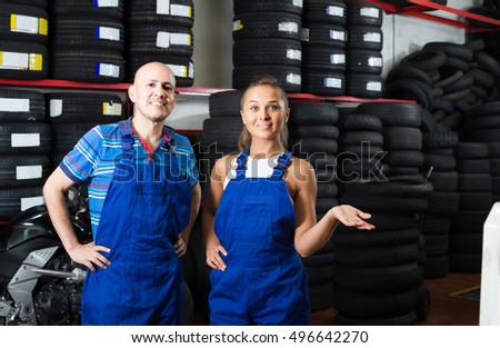 two cheerful european technicians in coveralls standing at car service point