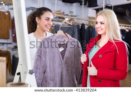Two cheerful female friends choosing warm jacket in shop and smiling
