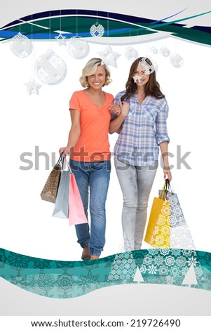 Two cheerful friends with shopping bags against christmas frame - stock photo
