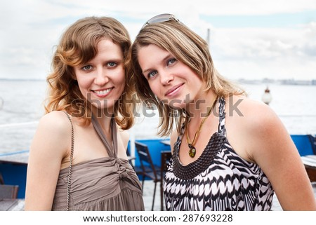 Two cheerful girlfriend have sea cruise on ship, standing at deck together - stock photo