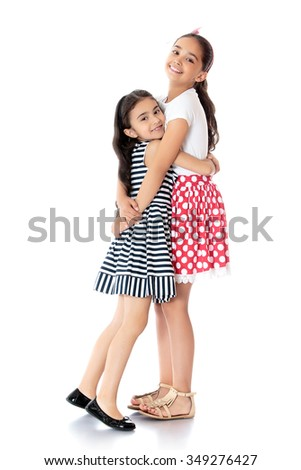 Two cheerful girls are sisters of different ages fun hug - Isolated on white background.The concept of a Happy childhood and child development