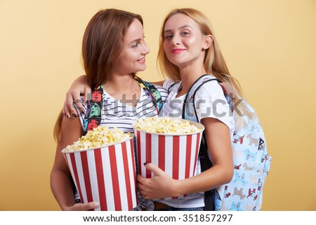 two cheerful girls eat popcorn from huge bowl