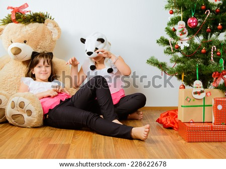 Two cheerful girls have a fun near Christmas tree - stock photo