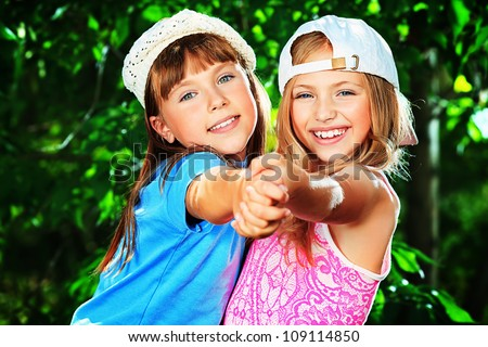 Two cheerful girls in a summer park. - stock photo