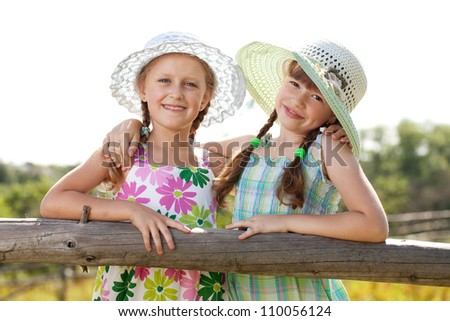 Two cheerful girls in hats and pigtails