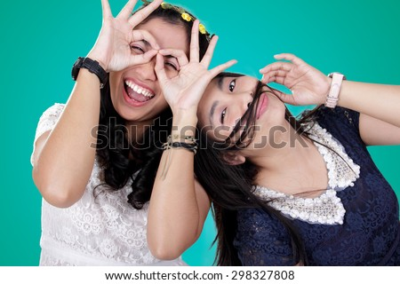 Two cheerful girls pose to camera with funny expression, over turquoise colored background - stock photo