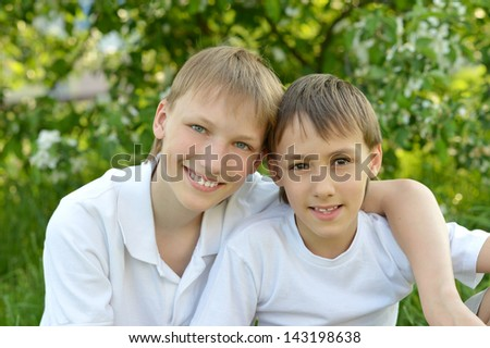 two cheerful guy resting on nature in summer - stock photo