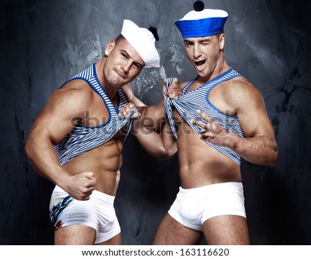 Two cheerful handsome sailors posing, looking at camera. - stock photo