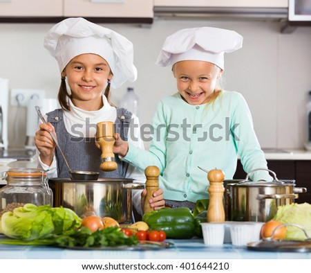 Two cheerful happy girls cooking vegetable soup at home kitchen - stock photo