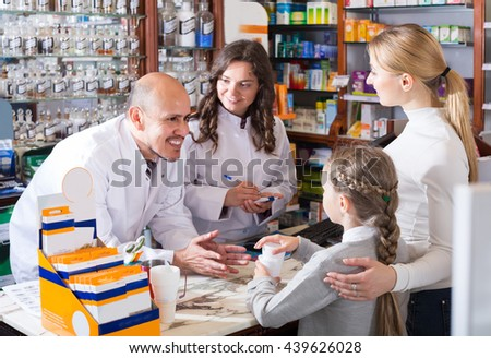 Two cheerful happy pharmacists helping a woman and a girl  in the pharmacy