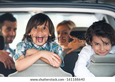 Two cheerful kids on a car backseat - stock photo