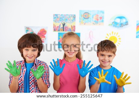 Two cheerful little boys and smiling girl showing at camera painted hands. Preschool center for children