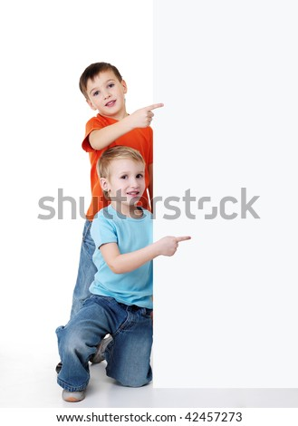 Two cheerful little boys look outs from the billboard and pointing on it. Fill-length portrait - stock photo