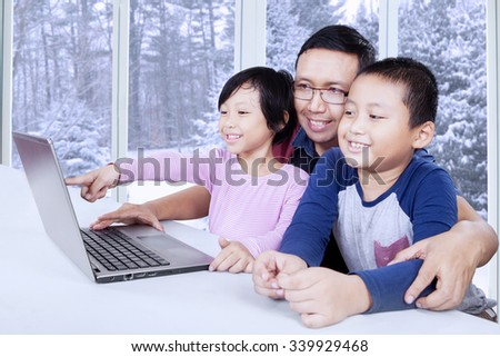 Two cheerful little children enjoy movie with their father by using laptop, shot at home - stock photo