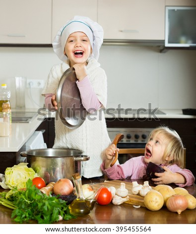 Two cheerful little sisters with pot smiling at home kitchen - stock photo