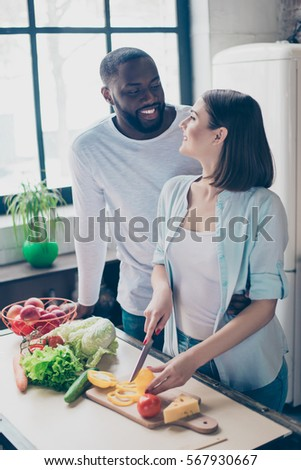 two cheerful mixed race people together cooking healthy breakfast. Handsome afro american guy  with his  beautiful caucasian girl  in kitchen