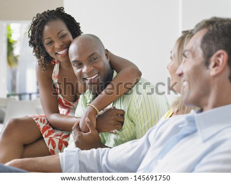 Two cheerful multiethnic couple chatting at home - stock photo