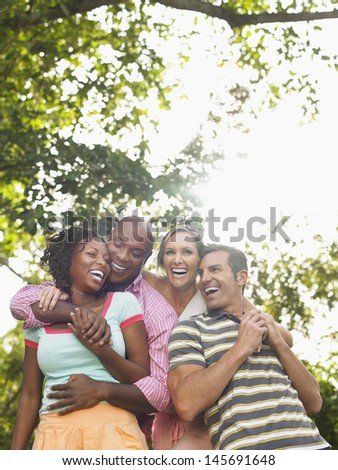 Two cheerful multiethnic couple embracing and laughing in garden - stock photo