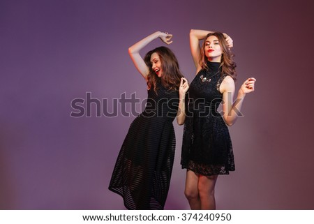Two cheerful pretty young women dancing and smiling over colorful background - stock photo