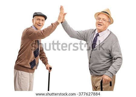 Two cheerful senior gentlemen high-five each other and looking at the camera isolated on white background - stock photo