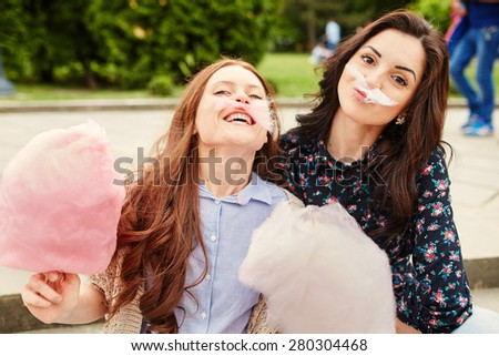 Two cheerful sisters eating cotton candy at the park - stock photo