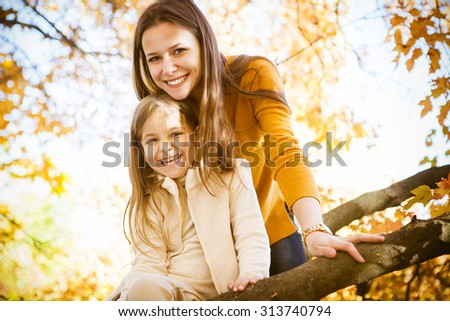 Two cheerful sisters playing in the park in warm autumn day
