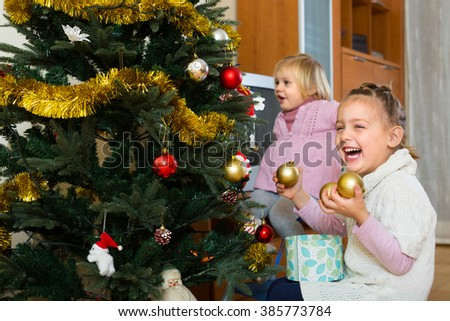 Two cheerful smiling little sisters decorating Christmas tree at home - stock photo