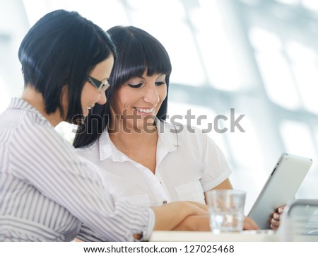 Two cheerful smiling young business women working on tablet pc - stock photo