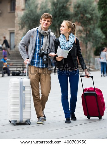 Two cheerful smiling young travelers with city map and baggage looking for hotel - stock photo