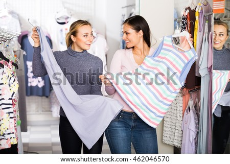 Two cheerful smiling young women selecting comfortable pajamas in underwear store