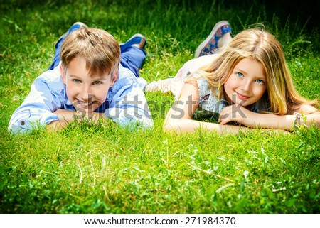 Two cheerful teenagers on the grass in the park. Summer. Friendship. - stock photo