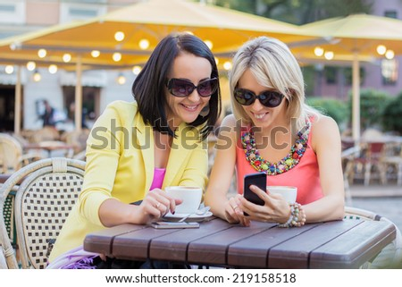 Two cheerful women having friendly chat in cafe - stock photo