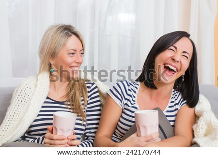 Two cheerful women laughing while sitting comfortably in bed - stock photo