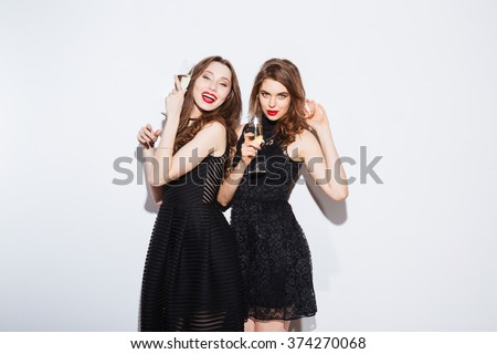 Two cheerful women posing in night dress with glass of champagne isolated on a white background - stock photo