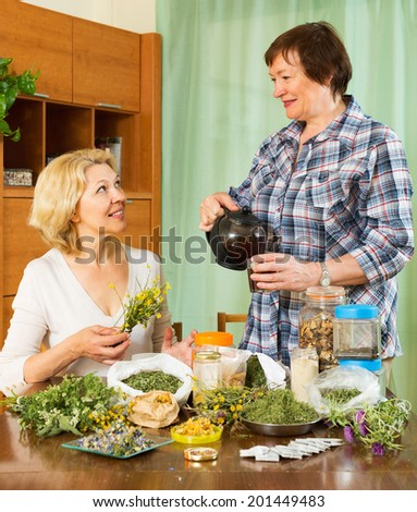 Two cheerful women sitting at the table with herbal tea and herbs