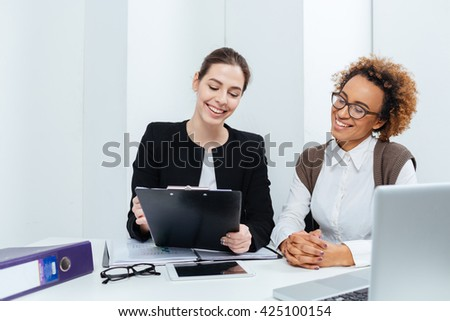 Two cheerful young businesswomen with clipboard working together in office - stock photo