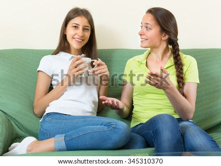 Two cheerful young girlfriends gossiping and smiling sitting on a sofa at home - stock photo