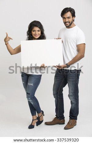 Two cheerful young Indian people holding a blank billboard white background - stock photo