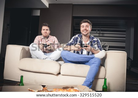 Two cheerful young men playing video games while sitting on sofa - stock photo