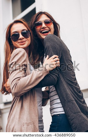 Two cheerful young woman against a white wall. city - stock photo