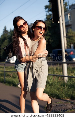Two cheerful young women walking on the street.  Best friends