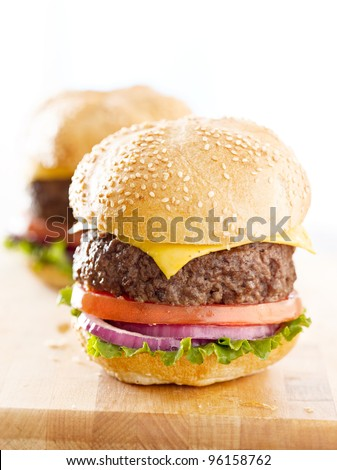 Two cheeseburgers on a wooden surface. - stock photo