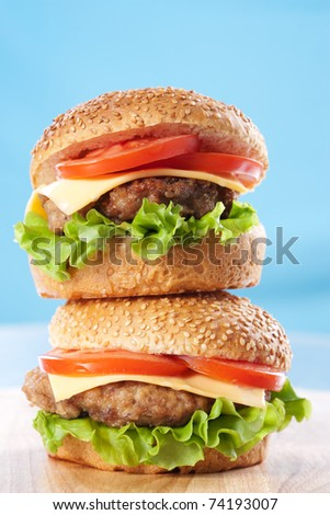 Two cheeseburgers with tomatoes and lettuce on a wooden table with blue background