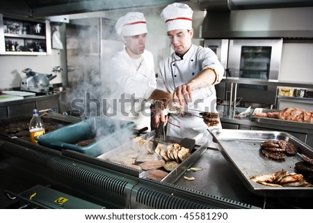 Two chefs at work in a restaurant - stock photo