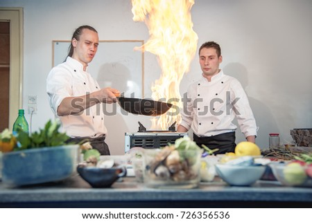 Two Chefs Flaming The Dishes In Their Kitchen Frying Some Exotic Food