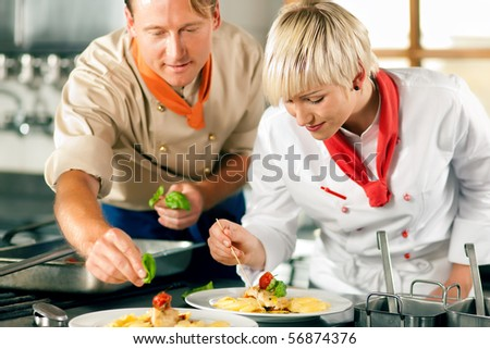 Two chefs in teamwork - man and woman - in a restaurant or hotel kitchen cooking delicious food, both are finishing the dishes - stock photo