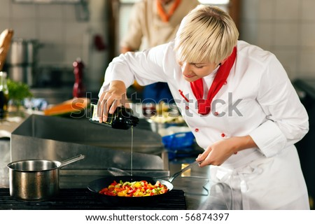 Two chefs in teamwork - man and woman - in a restaurant or hotel kitchen cooking delicious food, she is putting olive oil in the ratatouille - stock photo