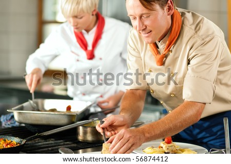 Two chefs in teamwork - man and woman - in a restaurant or hotel kitchen cooking delicious food, both are finishing the dishes
