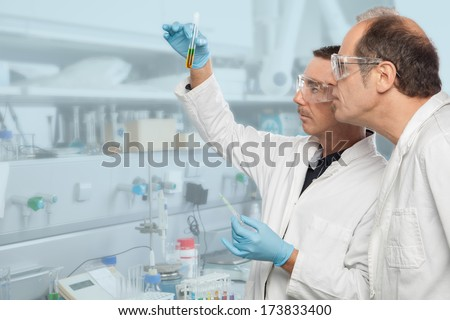 Two chemists are analyzing a liquid mixture in a test tube. - stock photo
