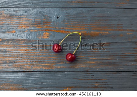 Two cherry on old wood. Healthy and tasty food on grey background. - stock photo